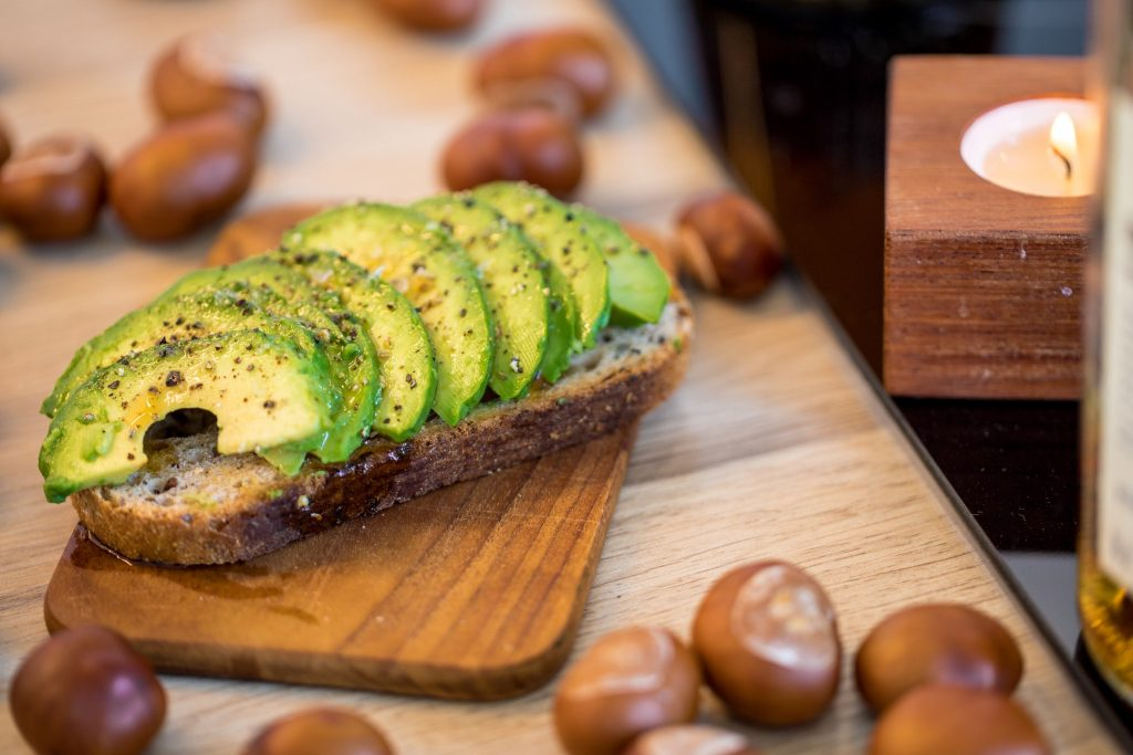 Wooden cutting board with sliced avocado on it and hazelnuts scattered around the table