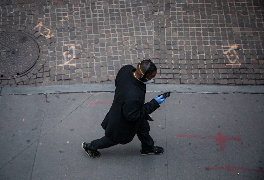 Birdseye view of a man walking down a street wearing a black coat, sneakers, headphones, a protective face mask and hospital gloves looking at his cell phone.