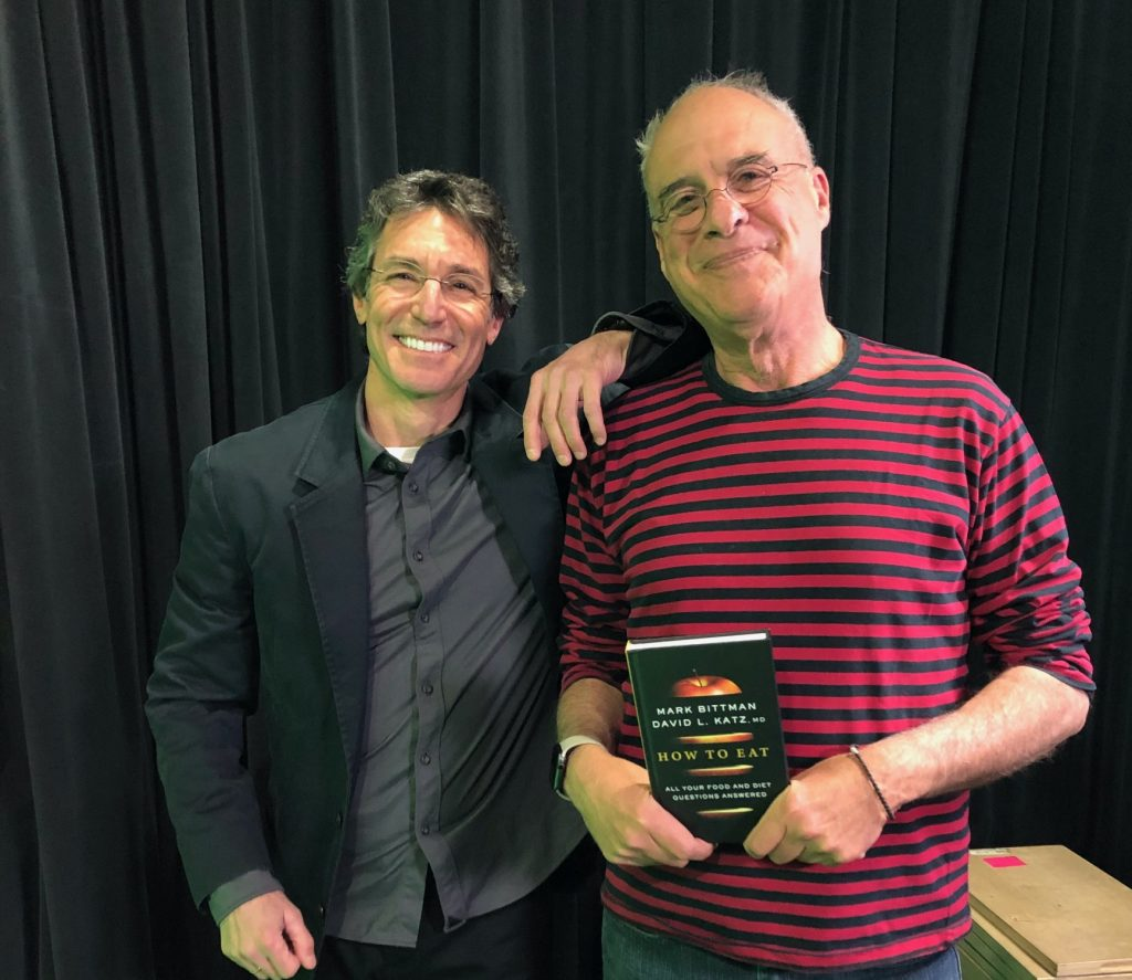 "David L Katz MD on left and Mark Bittman on righ, holding a copy oof their new book, ""How to Eat: All Your Food and Diet Questions Answered."""
