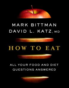 How to Eat Book Cover: black background, red apple sliced horizontally with authors and title written in between the slices