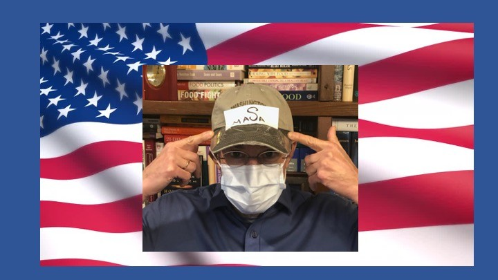 """Dr. Katz wearing a facemask points to his baseball cap with a """"MASA"""" (Make America Safe Again) sign. US Flag in the background."""