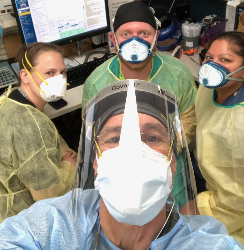 Dr. Katz in full PPE - mask and shield taking a selfie with 3 other healthcare workers in the background, smiling at camera
