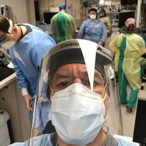 Dr. Katz in full PPE - mask and shield - and other healthcare workers in the background, working on patients