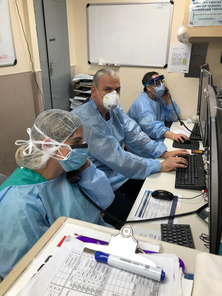 3 healthcare workers in full PPE typing and looking on computers in office area of emergency room.
