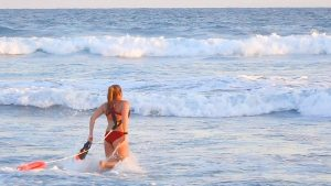 Female lifeguard in red bathing suit with two life buoys runs into the ocean beach water