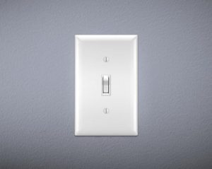 "Light switch on gray wall. Switch is ""on."""