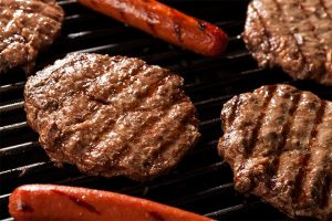 Close up of a grill with 4 hamburgers and 2 hotdogs