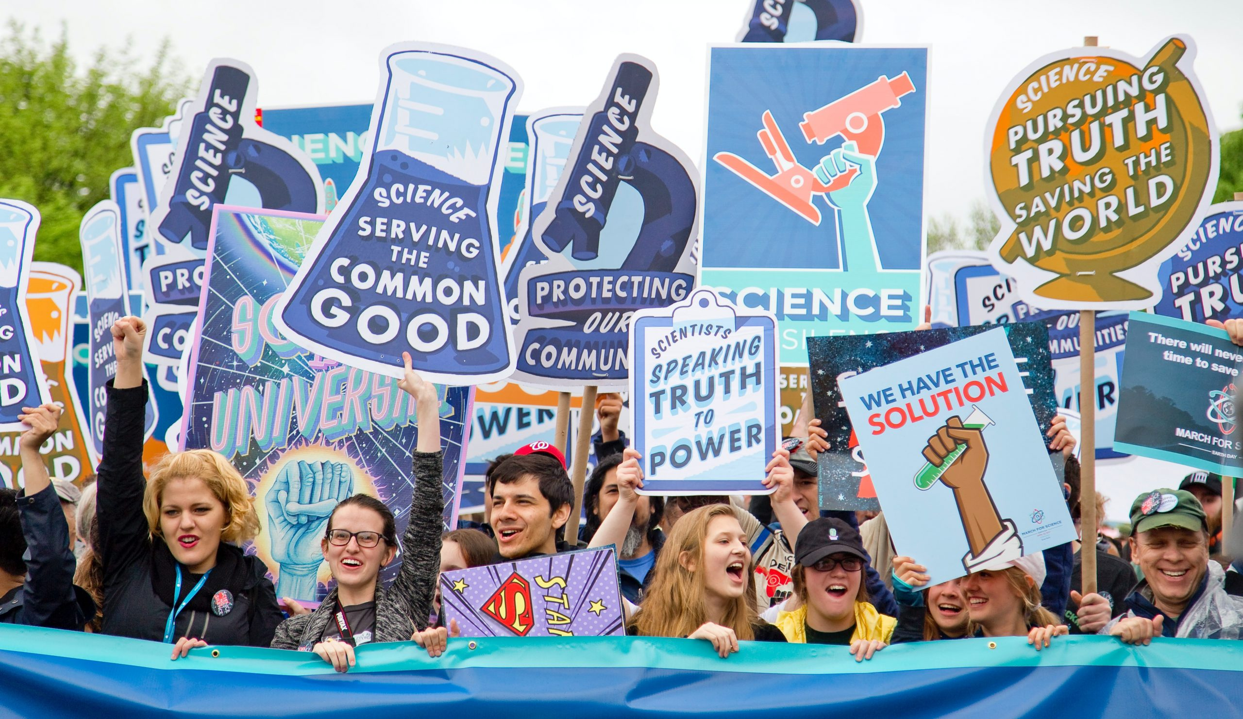"Young protestors smiling and holding up ""truth"" and ""science"" signs."