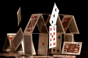 A house of (playing) cards on a table, black background; top cards are toppling over.
