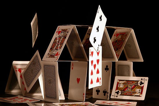 """A """"house of (playing) cards against a black backdrop, the top cards starting to fall over."""