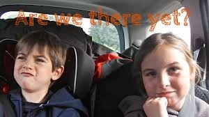 "Two impatient-looking children in the back seat of a car with ""Are We There Yet?"" text above their heads."