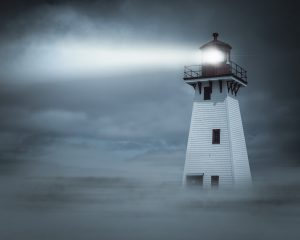 Lighthouse shining a light through the night in a thick fog.