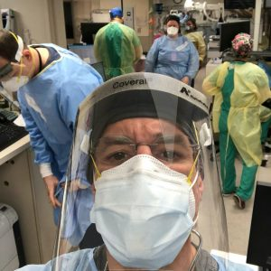 Image of David Katz, MD in full PPE gear with hospital personnel in background, also wearing full gear.