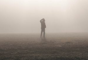 Silhouette of a person walking along a foggy field, hand scratching his/her head