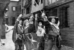 Black and white image of the 4 muskateers raising their swords in unison.