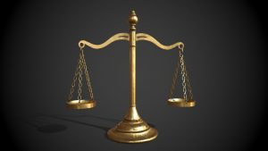 """Antique brass """"scale of justice"""" with two empty brass trays hanging by chains on either side. Black background."""