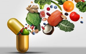 A golden pill capsule opens and out spills a variety of veggies and fruit