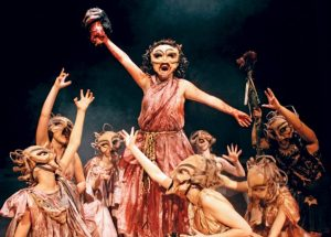 Opera scene where all characters are wearing masks, lifting up main character above the others