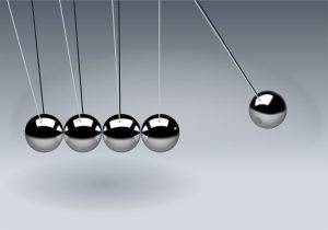 """Closeup of a """"Newtons Cradle"""" pendulum with 5 steel balls hanging, the right one separated to the right of the others, and a white background."""