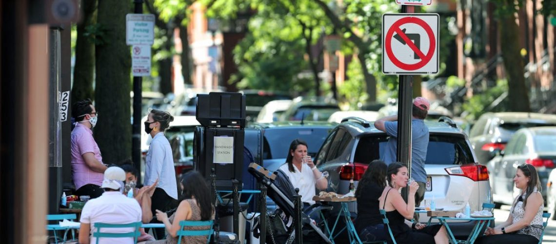 Busy city street corner; restaurant's outdoor seating getting filled after Covid-19 shutdown.