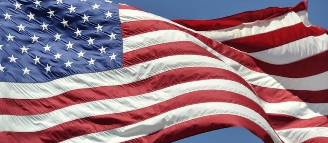 Closeup of the United States of America flag waving in the breeze, stars on the left side, on a sky blue background.
