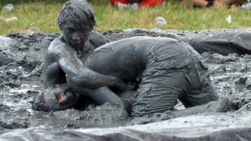 Two mud wrestlers wrestling and soaked in mud.