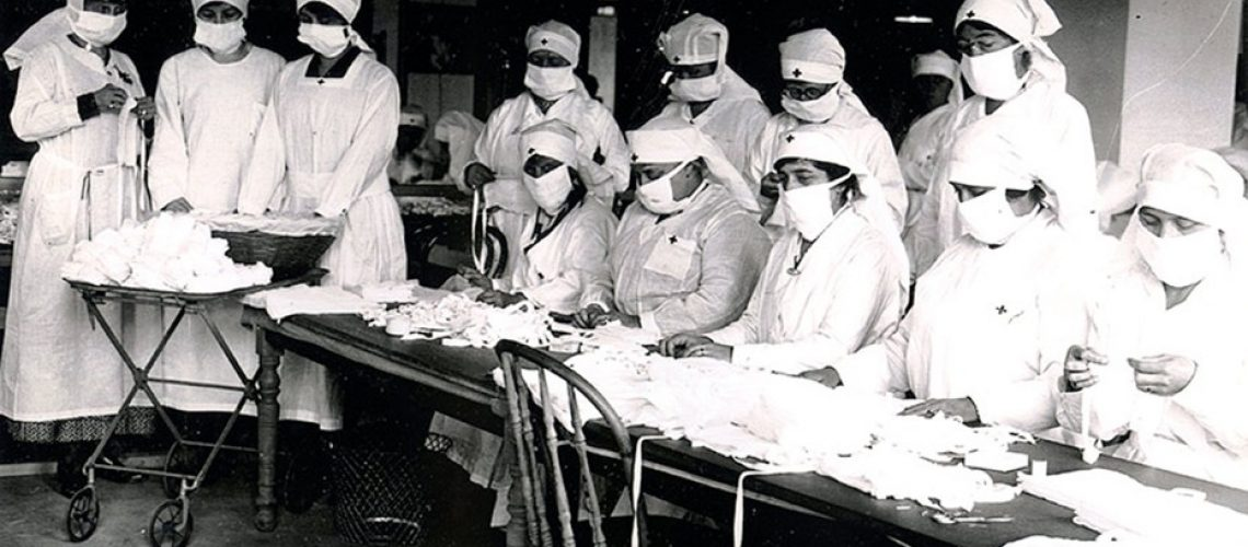 Black and white image of nurses in surgery garb folding face masks
