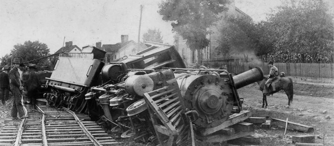 Black and White image of a derailed steam locamotive