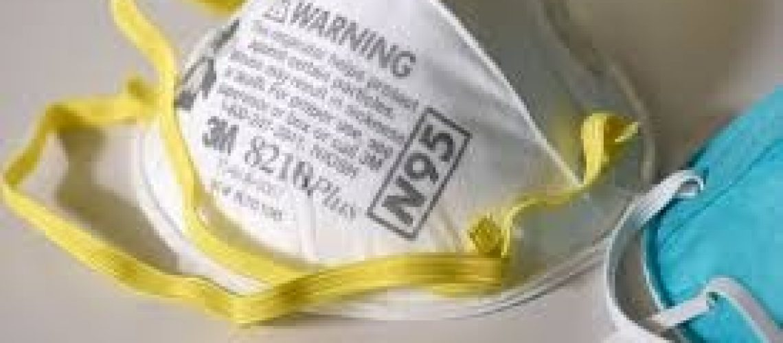 Close up of a white respiratory mask with yellow strap on a beige formica counter