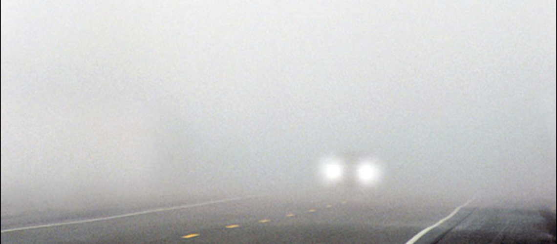 Foggy road with one set of headlights approaching the camera