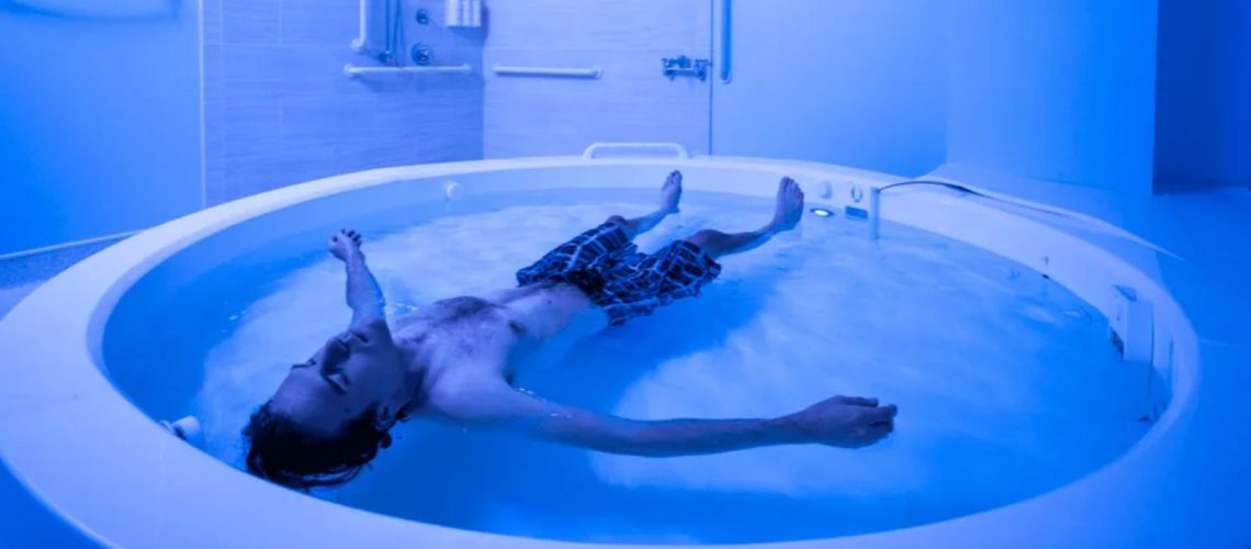 Dr. Justin Feinstein article: youn man in boxer shorts style bathing suit floats in a therapeutic floating pool in a blue-hue lit room.