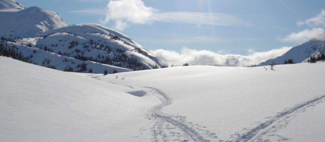 Snowy landscape on a sunny day with rocky hills on the back left and right, cross country ski tracks through the snow.