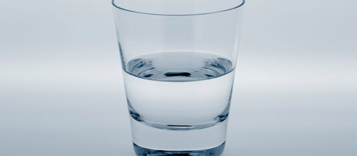 A glass of water on a white background: half full or half empty
