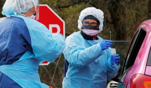 Two medical workers in full protective gear, with blue gowns, blue gloves, masks and hair covers, point a swab towards the driver side window of a car to test for Coronavirus.