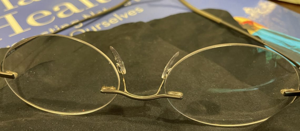 Pair of gold-rimmed oval reading glasses atop a brown eyeglass cleaning cloth and a small stack of magazines.